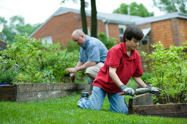 Adult and child working in garden